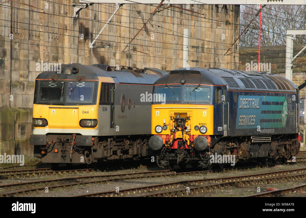 Class 57 diesel electric locomotive in DRS livery and class 92 electric British rail two-tone grey livery wait for their next duty Carlisle station. - Stock Image
