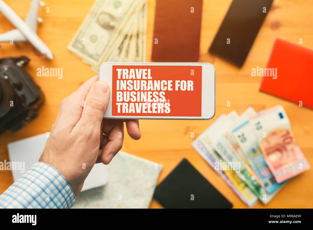 Travel insurance for business travelers online mobile phone app. Man holding smartphone with mock up application screen related to holiday vacation jo - Stock Image