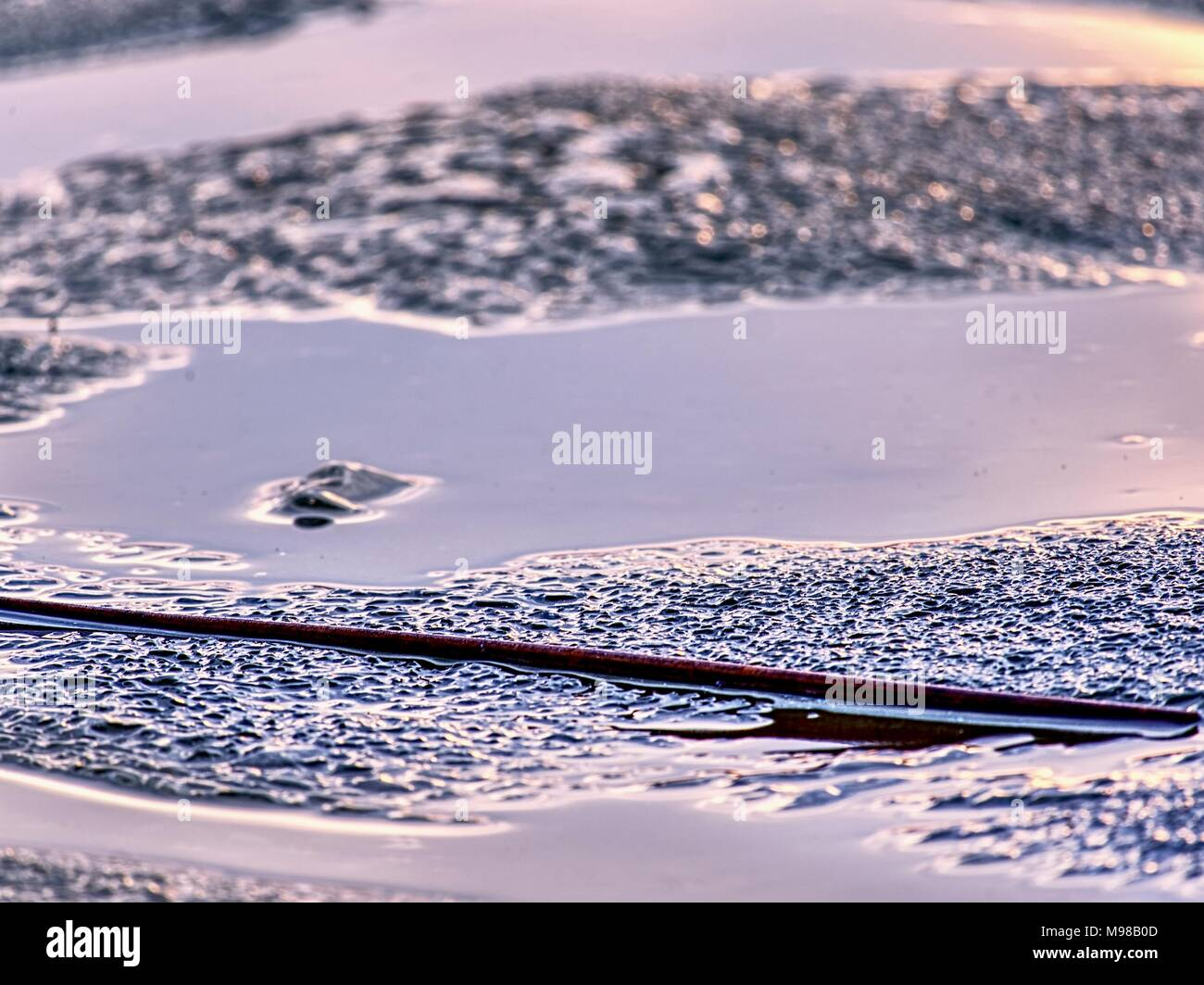Thaw edge. Sunset colors in ice floe.  Icy fragments are melting on flow ice and dark laggon water - Stock Image