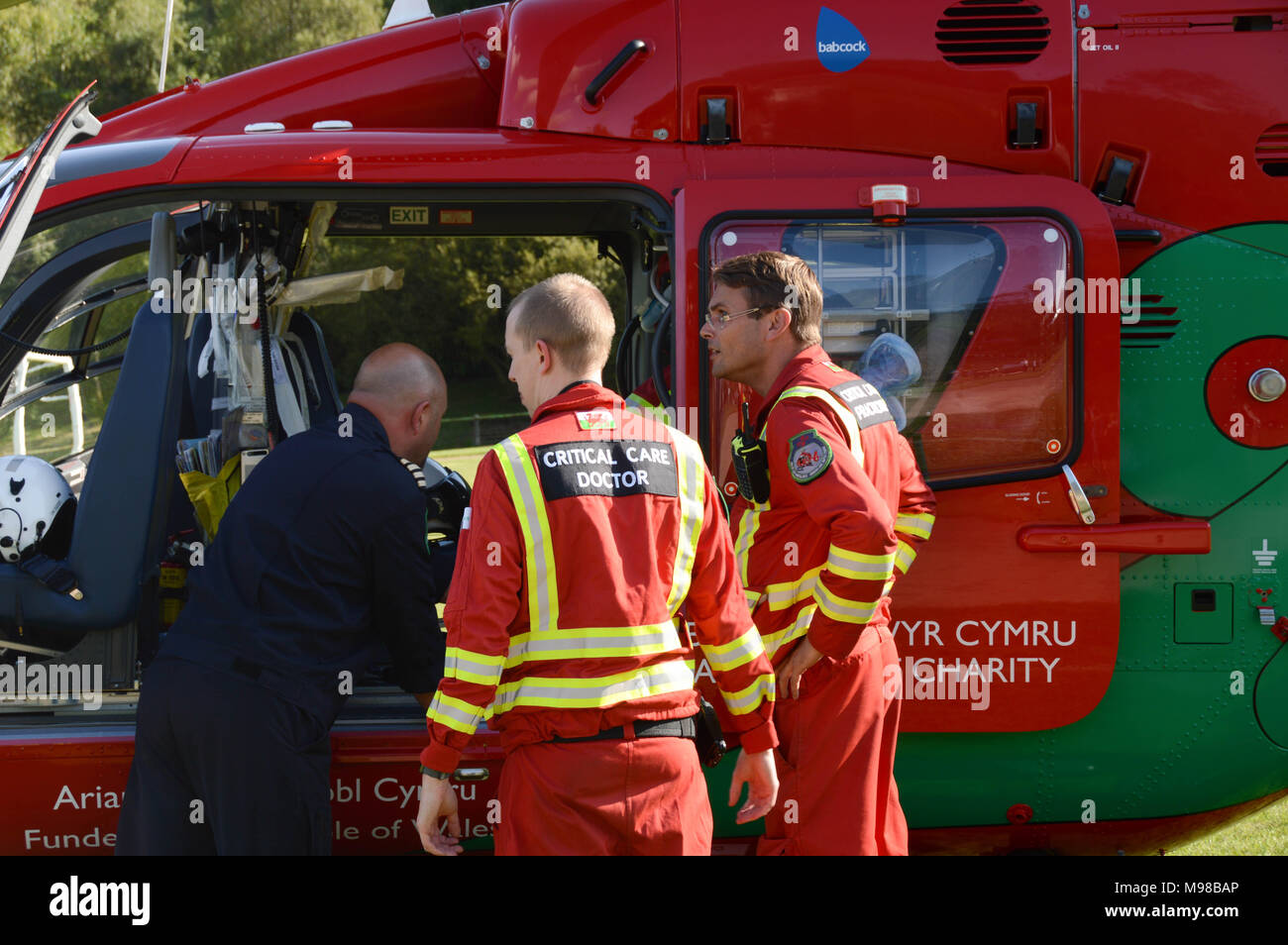 Medical crew members and the pilot outside a helicopter of the Wales Air Ambulance service Stock Photo