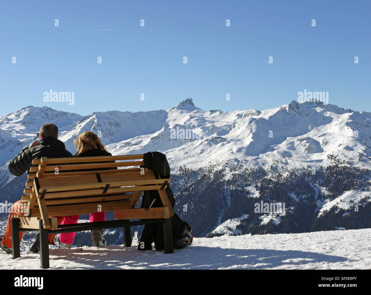 The swiss ski and snow-sport linked resort of St Luc and Chandolin in the Valais region of Switzerland.  Skiers relaxing and looking towards Grimentz Stock Photo