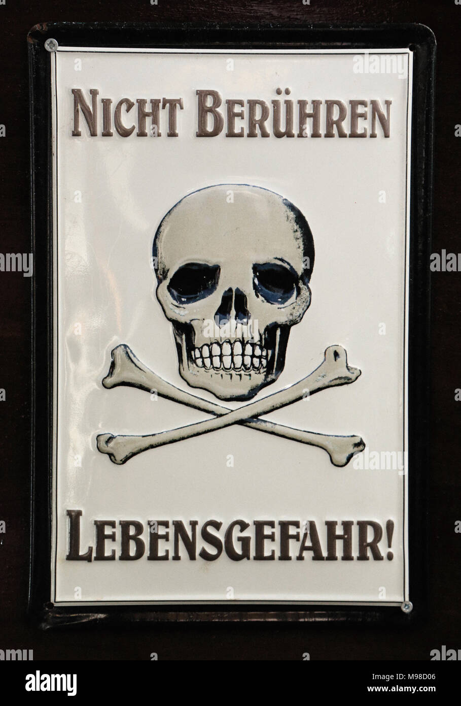 Skull with two crossed shinbone with the text written in German: Nicht Berühren Lebensgefahr, which translated means not touching, danger of death - Stock Image