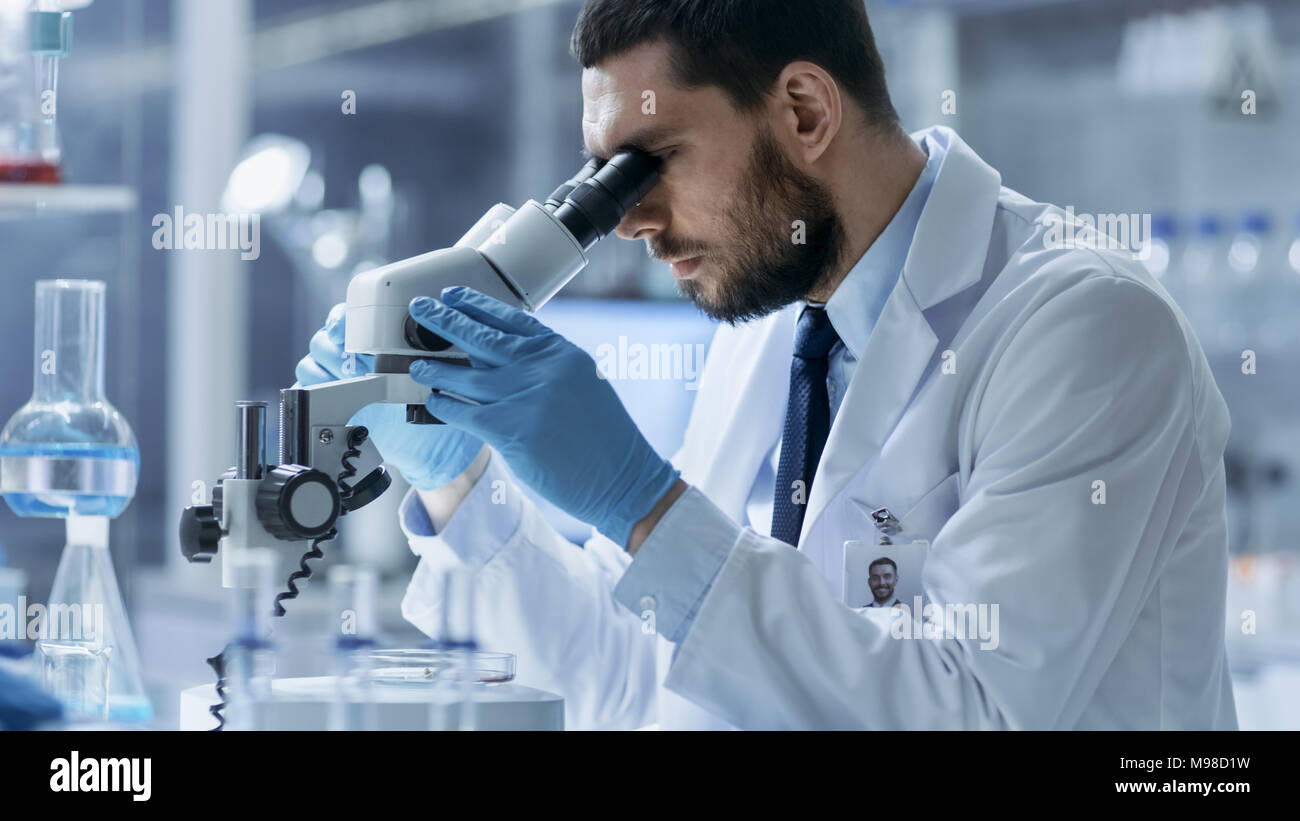 Research Scientist Looks into Microscope. He's Conducts Experiments in Modern Laboratory. - Stock Image