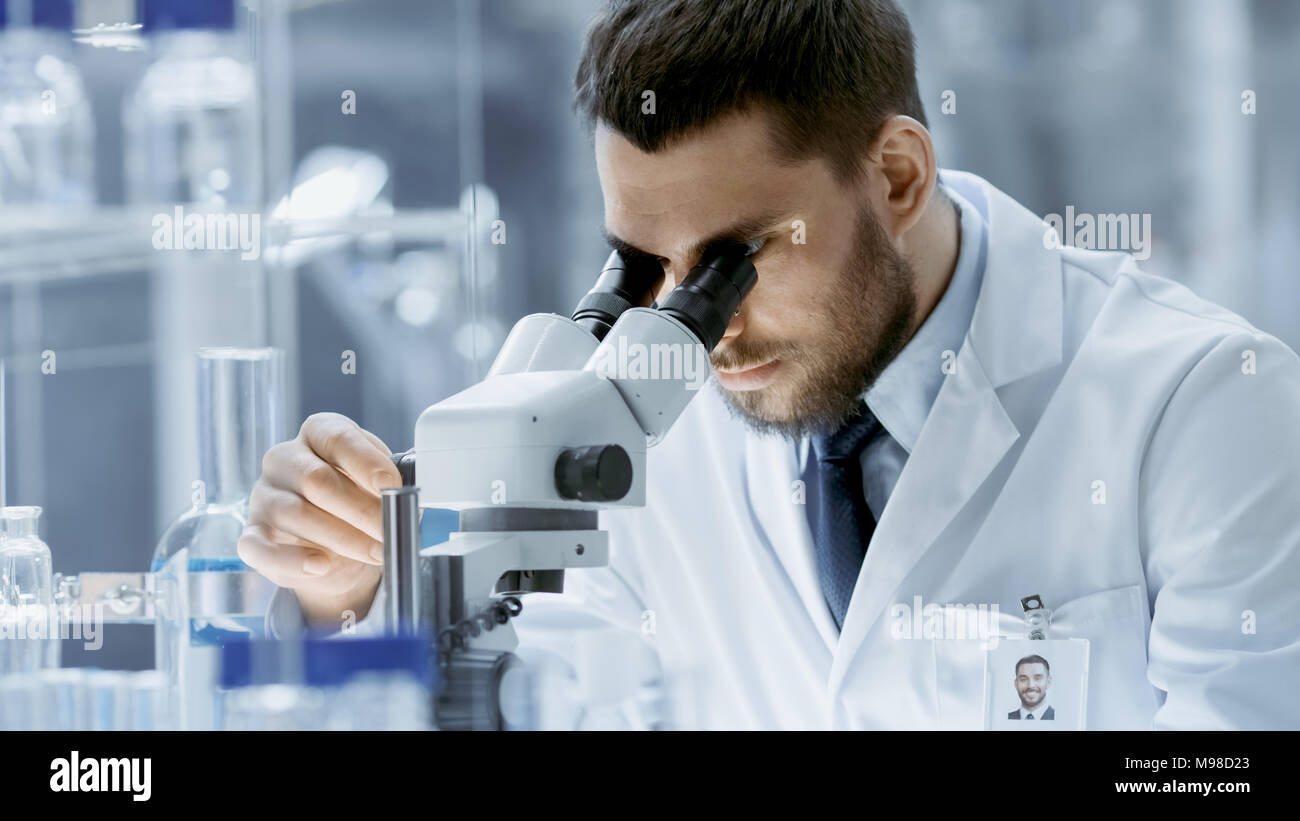 Close-up Shot of Research Scientist Adjusts His Microscope. He's Working in a High-End Modern Laboratory with Beakers, Glassware, Microscope, Monitors - Stock Image