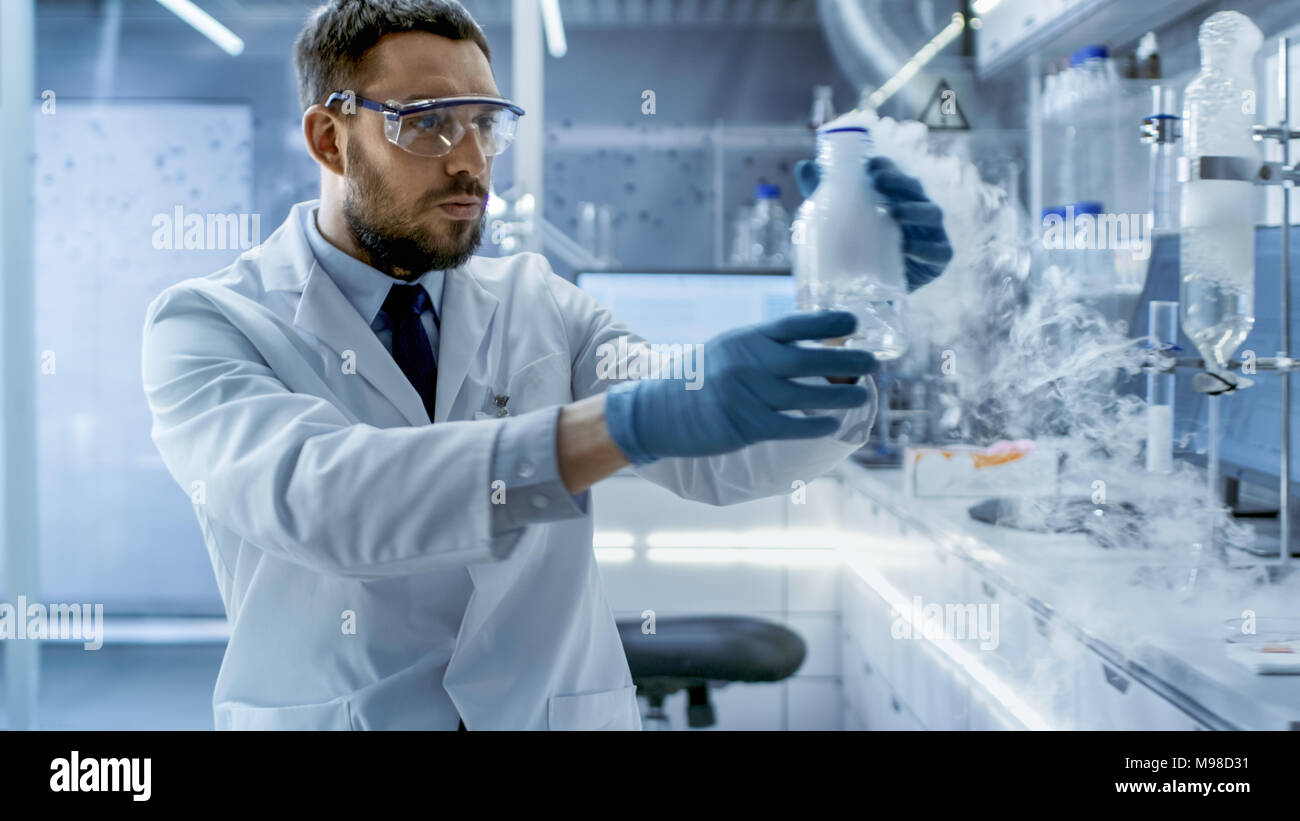 In a Chemical Research Laboratory Scientist Holds Smoking Compound in Beaker. - Stock Image