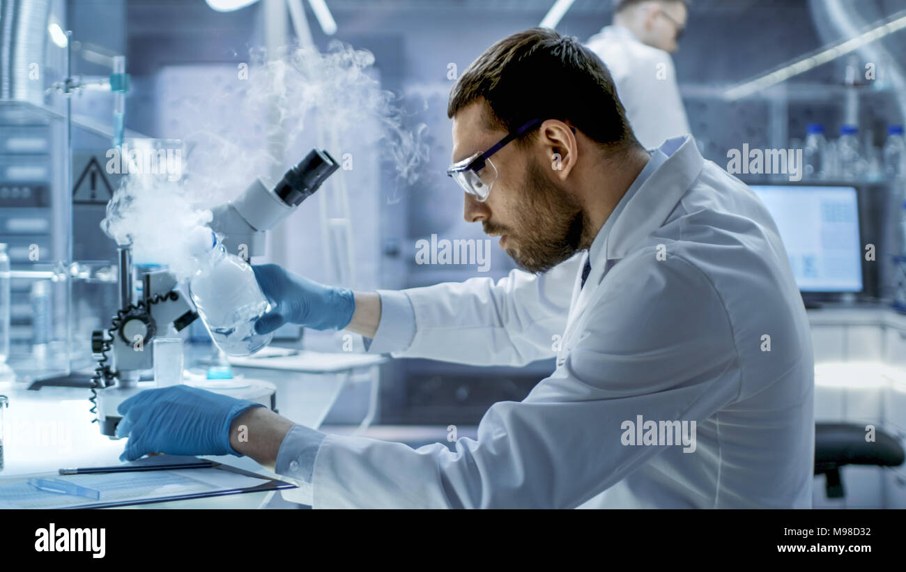 In a Chemical Research Laboratory Scientist Mixes Smoking Compounds in Beakers. - Stock Image
