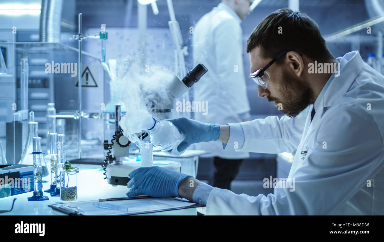 In a Chemical Research Laboratory Scientist Mixes Smoking Compounds in Beakers. Stock Photo