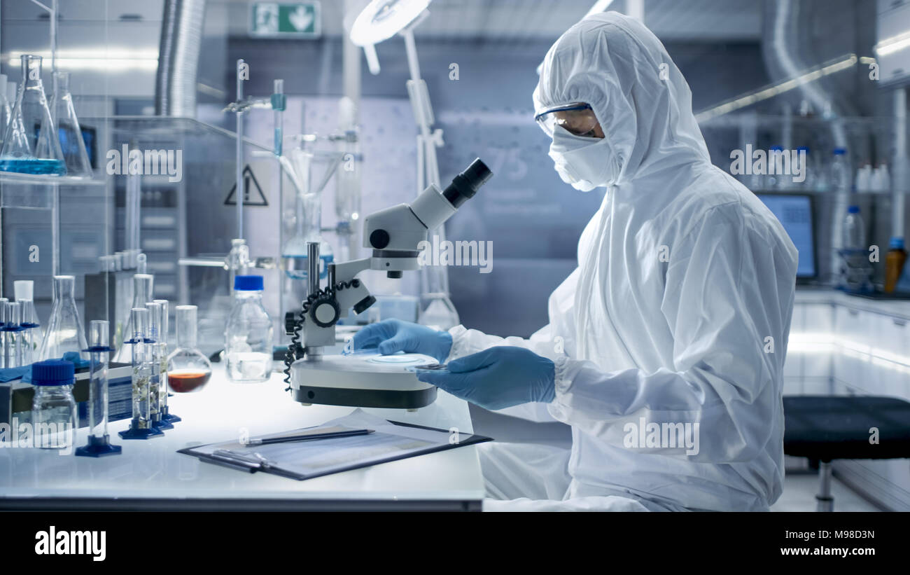 In a Secure High Level Laboratory Scientists in a Coverall Conducting a Research. Biologist Adjusts Samples in a Petri Dish with Pincers and Examines  Stock Photo