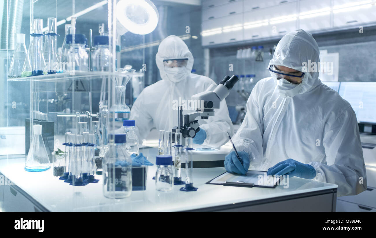 In a Secure High Level Laboratory Scientists in a Coverall Conducting a Research. Chemist Writes Down Experiment Results. Stock Photo