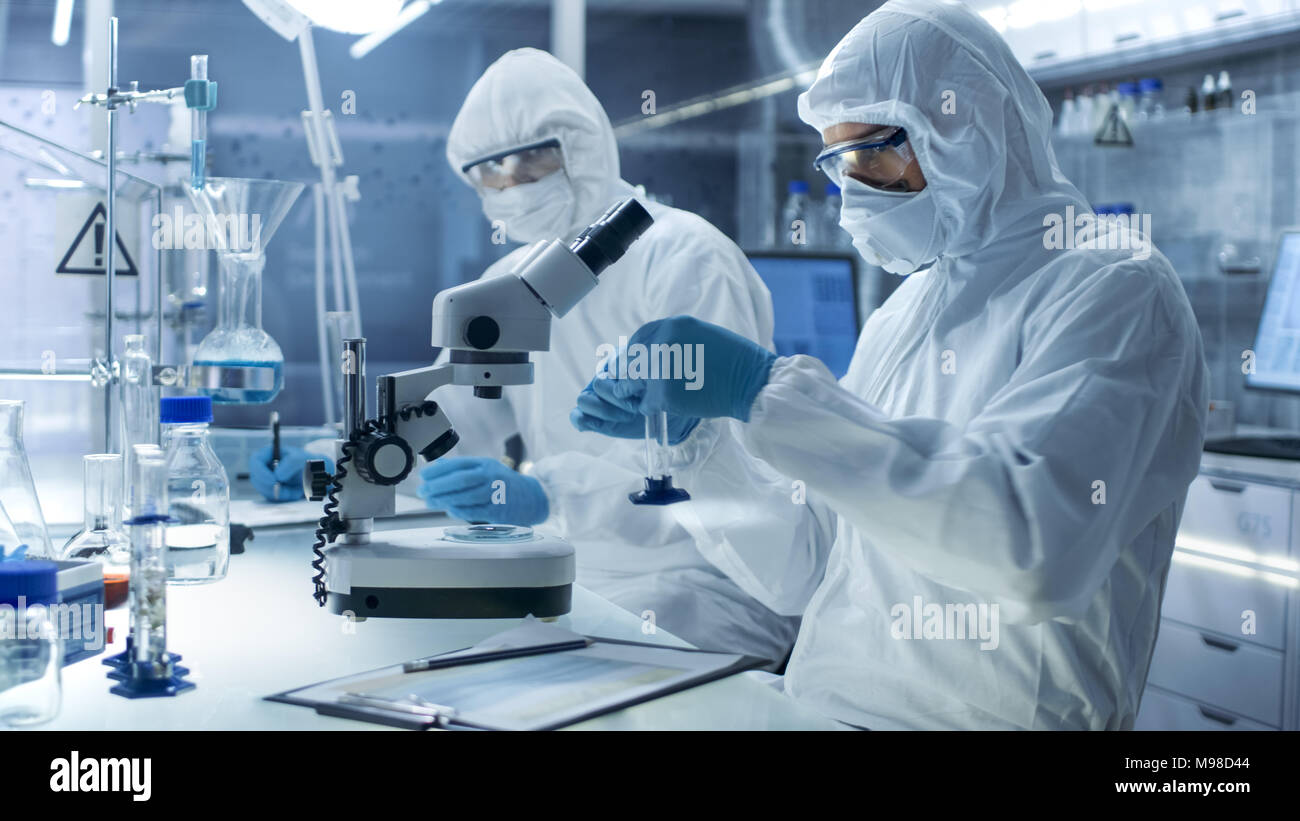 In a Secure High Level Laboratory Scientists in a Coverall Conducting a Research. Chemist Adjusts Samples and His Colleague Writes Down Results. - Stock Image