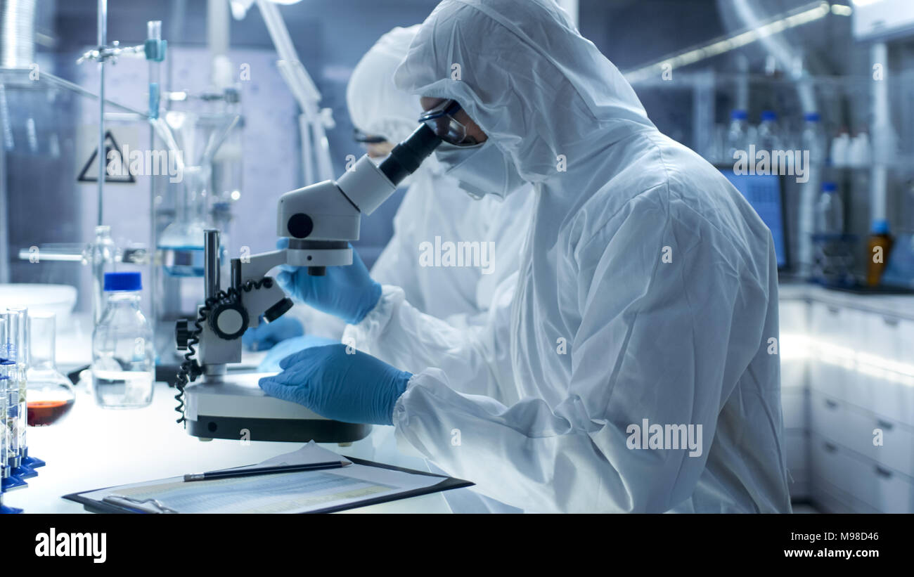 In a Secure High Level Laboratory Scientists in a Coverall Conducting a Research. Chemist Examines Samples Under Microscope and Colleague Results - Stock Image