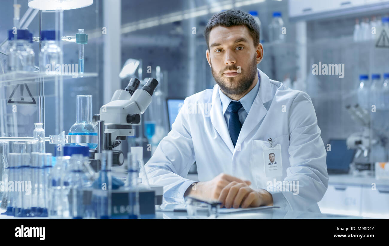 Young Male Research Scientist Talks Into Camera. He's Sitting in a High-End Modern Laboratory with Beakers, Glassware, Microscope and Working Monitors - Stock Image