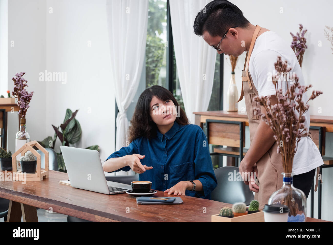 asian woman customer complaining to waiter about food in cafe restaurant,unhappy emotion service in coffee shop - Stock Image
