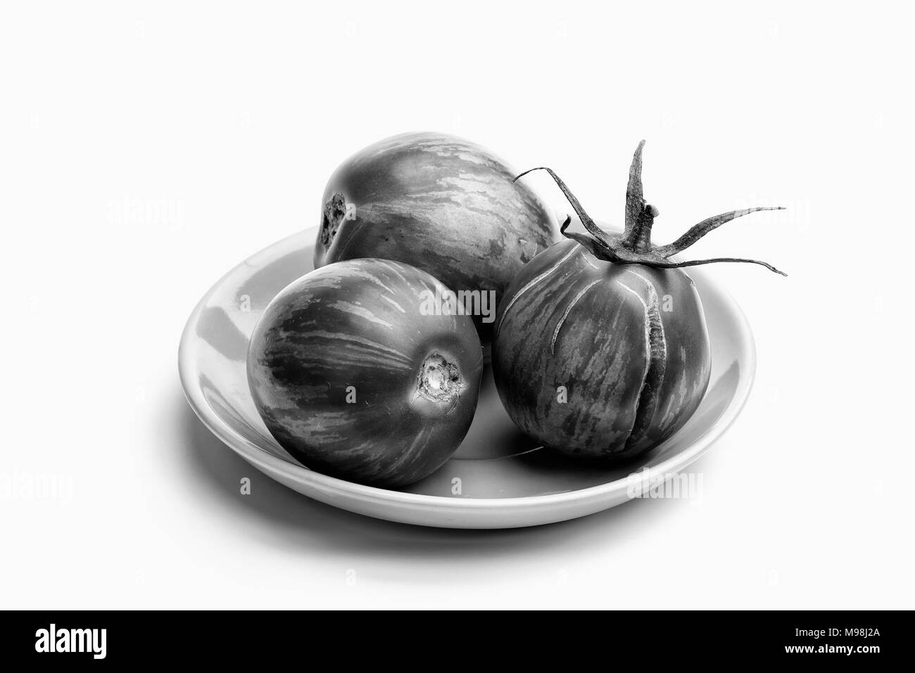 Three juicy zebra tomatoes in a little porcelain plate, isolated on white background - Stock Image