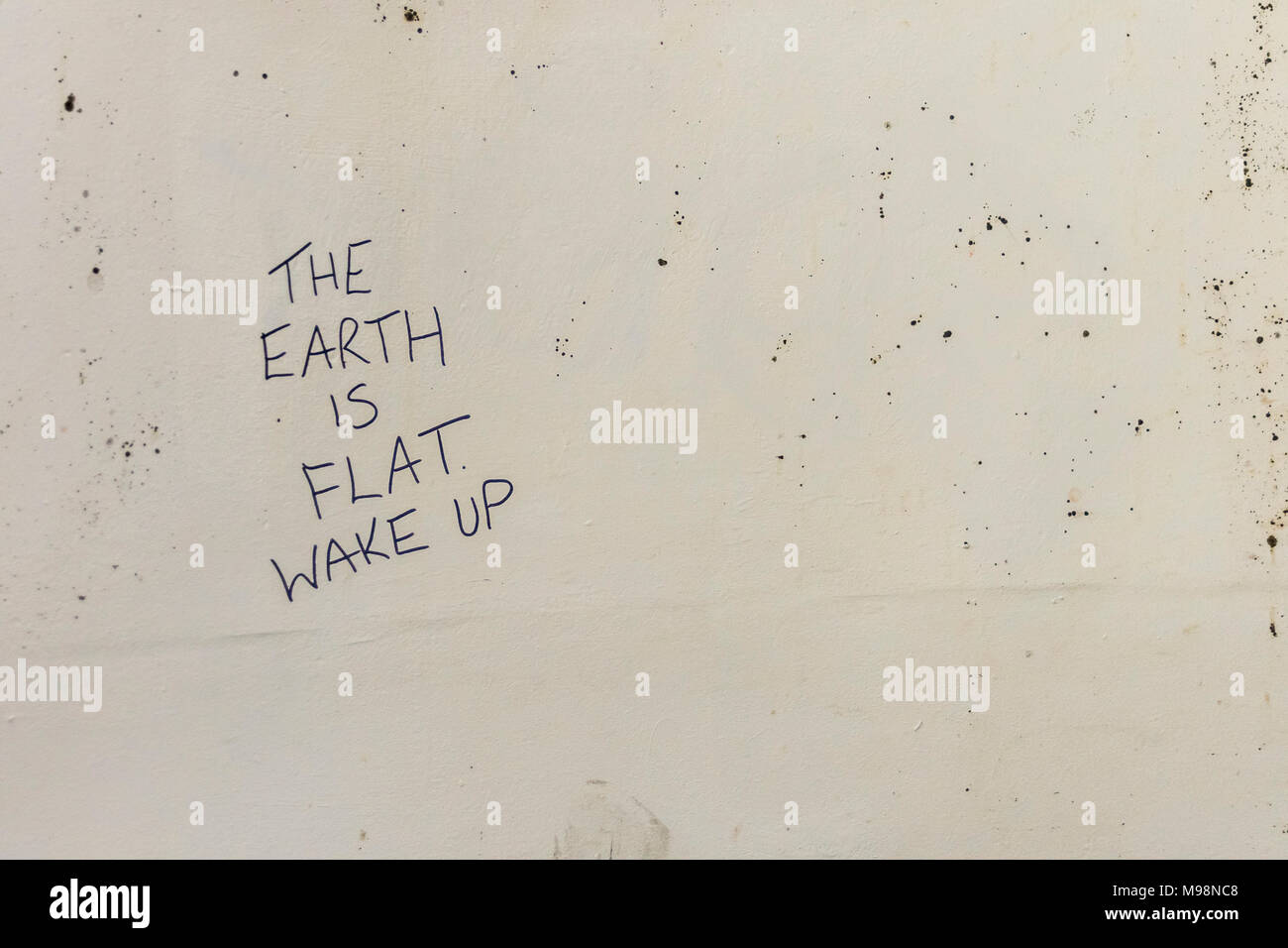 Profound urban philosophical graffiti scrawled on a Plymouth (Devon) wall - The Earth is Flat (perhaps metaphor for Flat Earth Society. :) - Stock Image