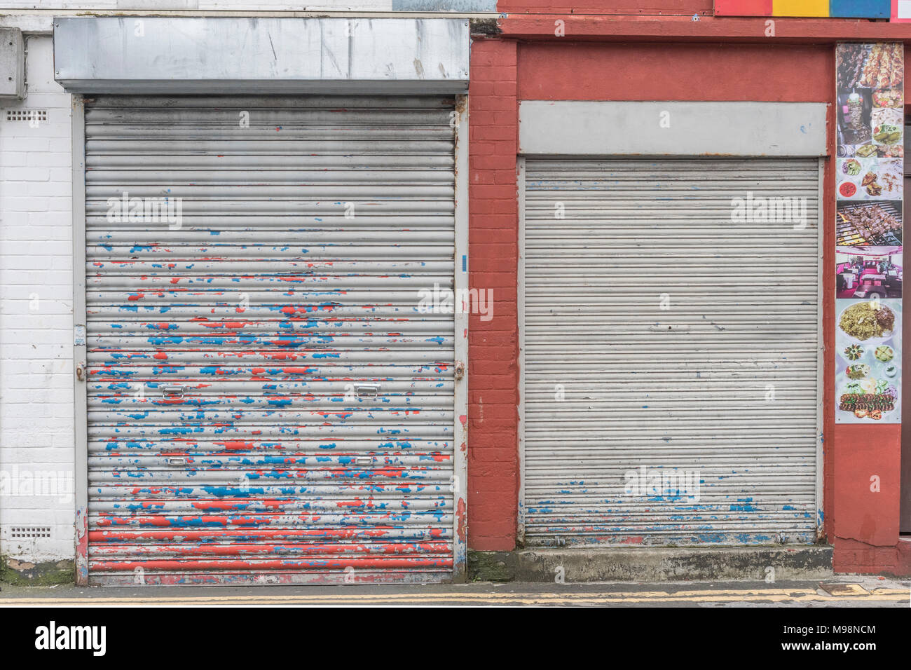 Battered closed roller shutter door with paint peeling off. Metaphor recession, high street closures, vacant shops. Obstructed or obstruction concept. Stock Photo