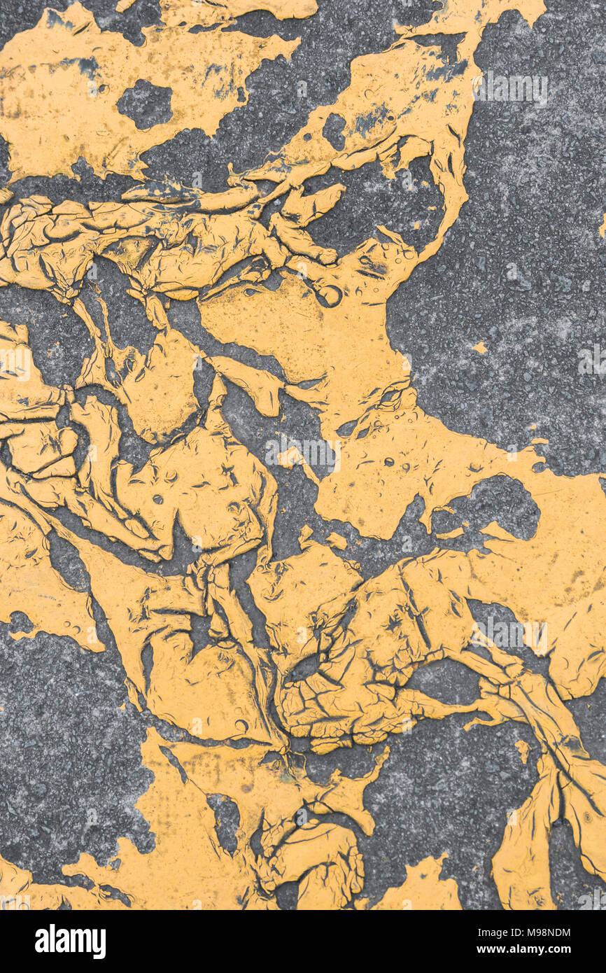 Abstract shapes of yellow thermoplastic road marking mastic on a pavement. - Stock Image