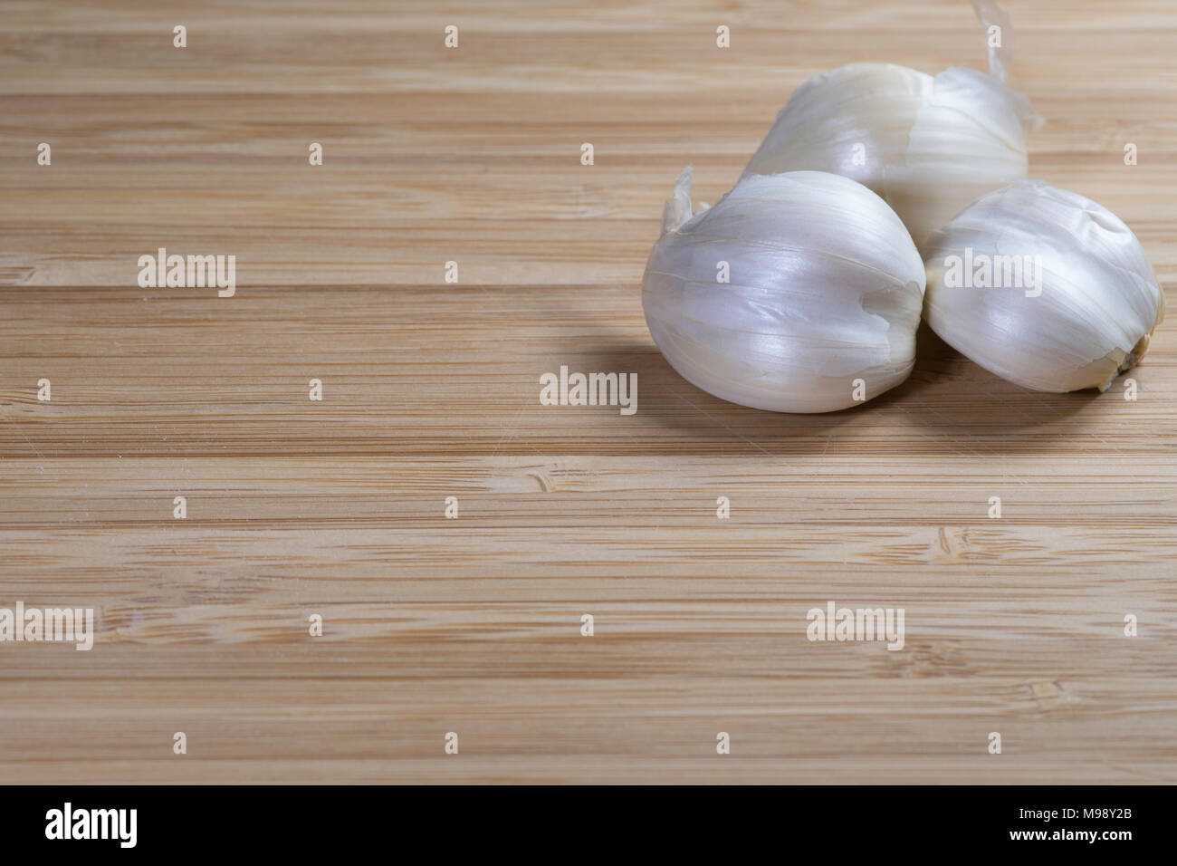 cloves of garlic on a bamboo cutting board background - Stock Image