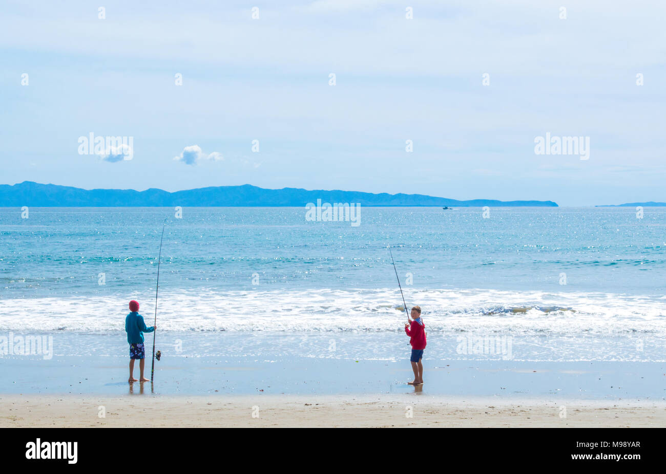 2 preteen Caucasian boys standing in the sand with fishing poles on a California USA beach with Anacapa Island in the distance - Stock Image