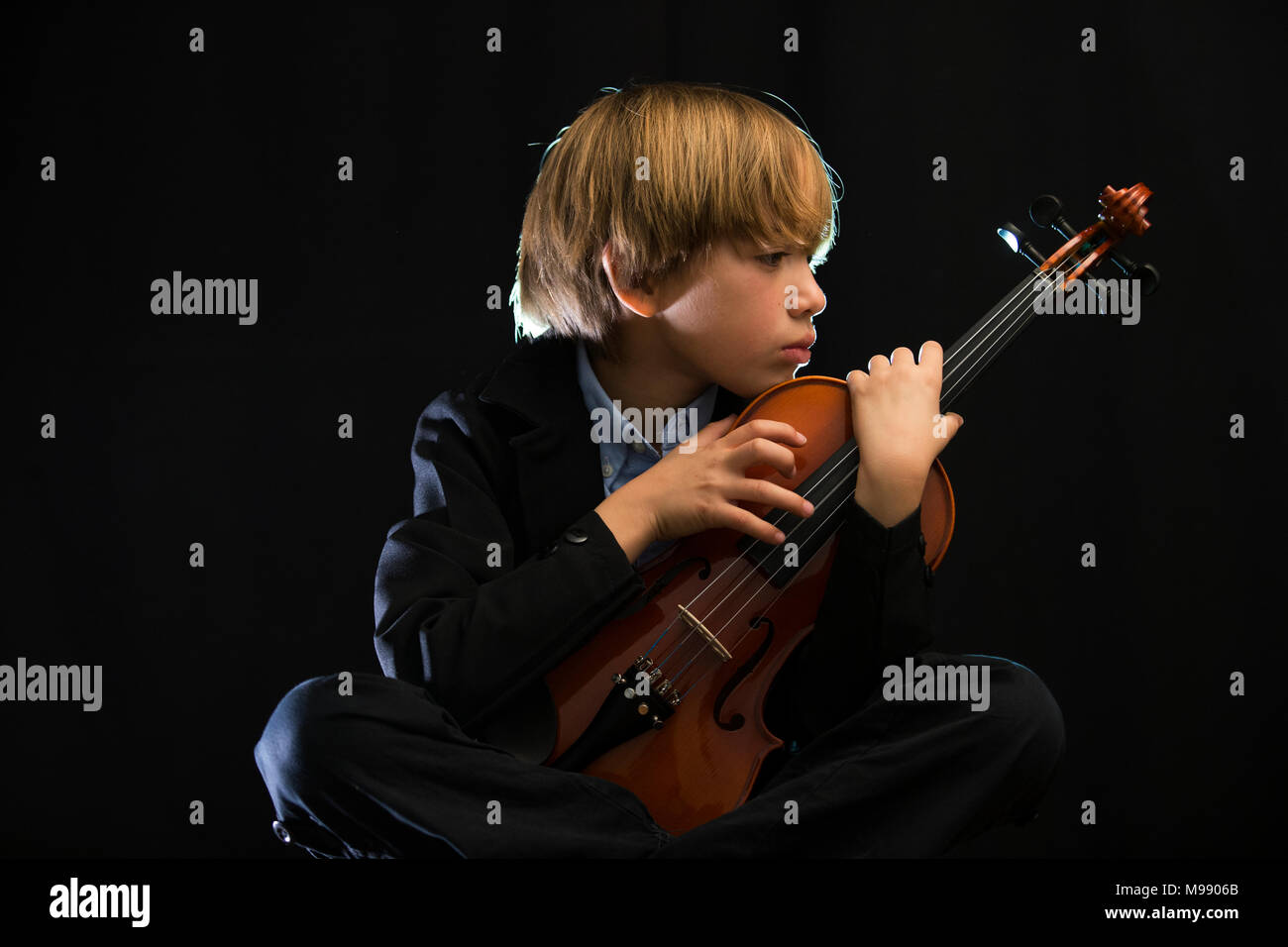child playing violin, black background, sentimental theme, sad, pensive, concentrated - Stock Image