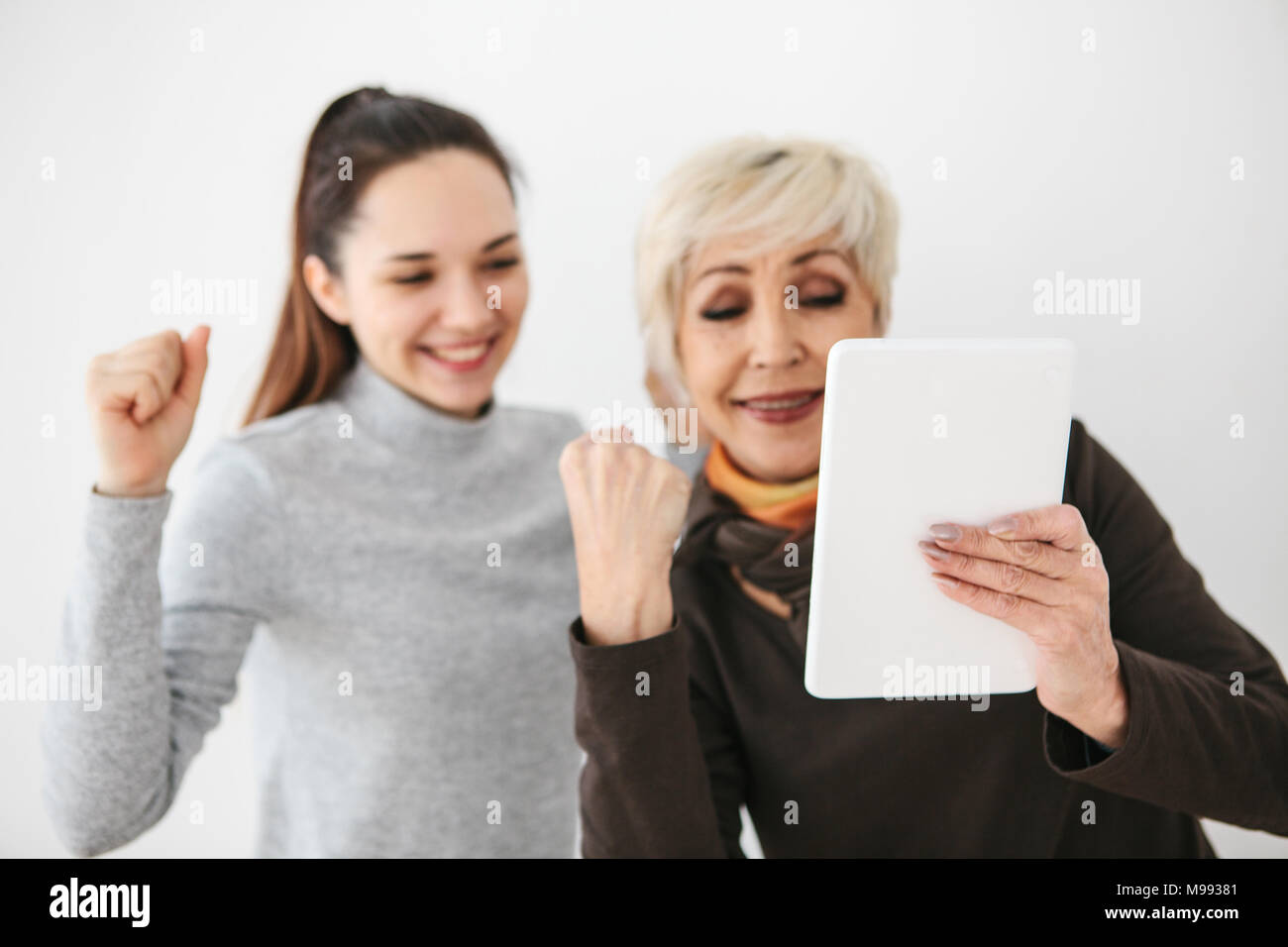 A young girl and an elderly woman look at something interesting on the tablet and are happy. Communication, joint pastime, positive emotions between people. - Stock Image