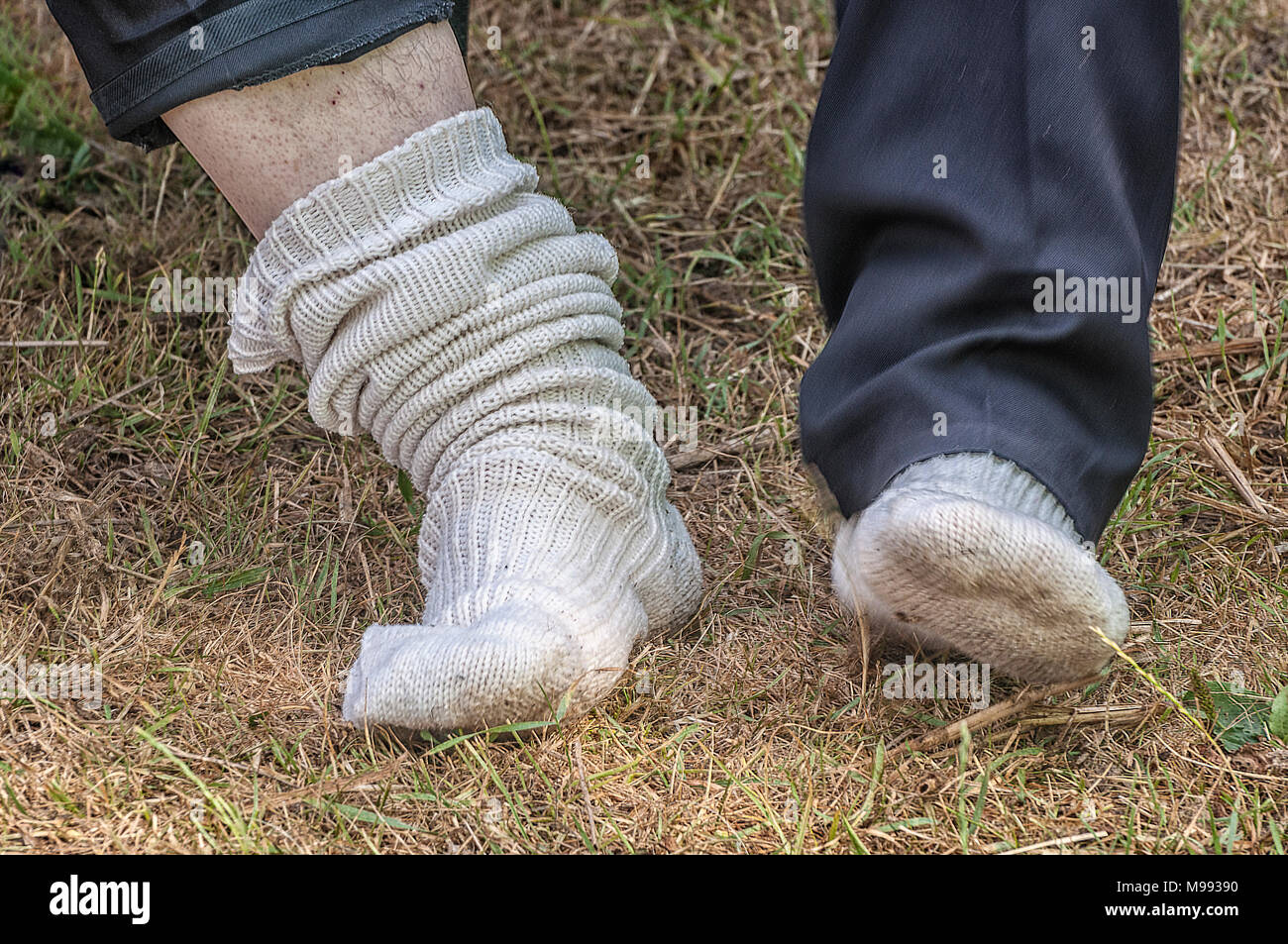 two thick feet with white wool socks on - Stock Image