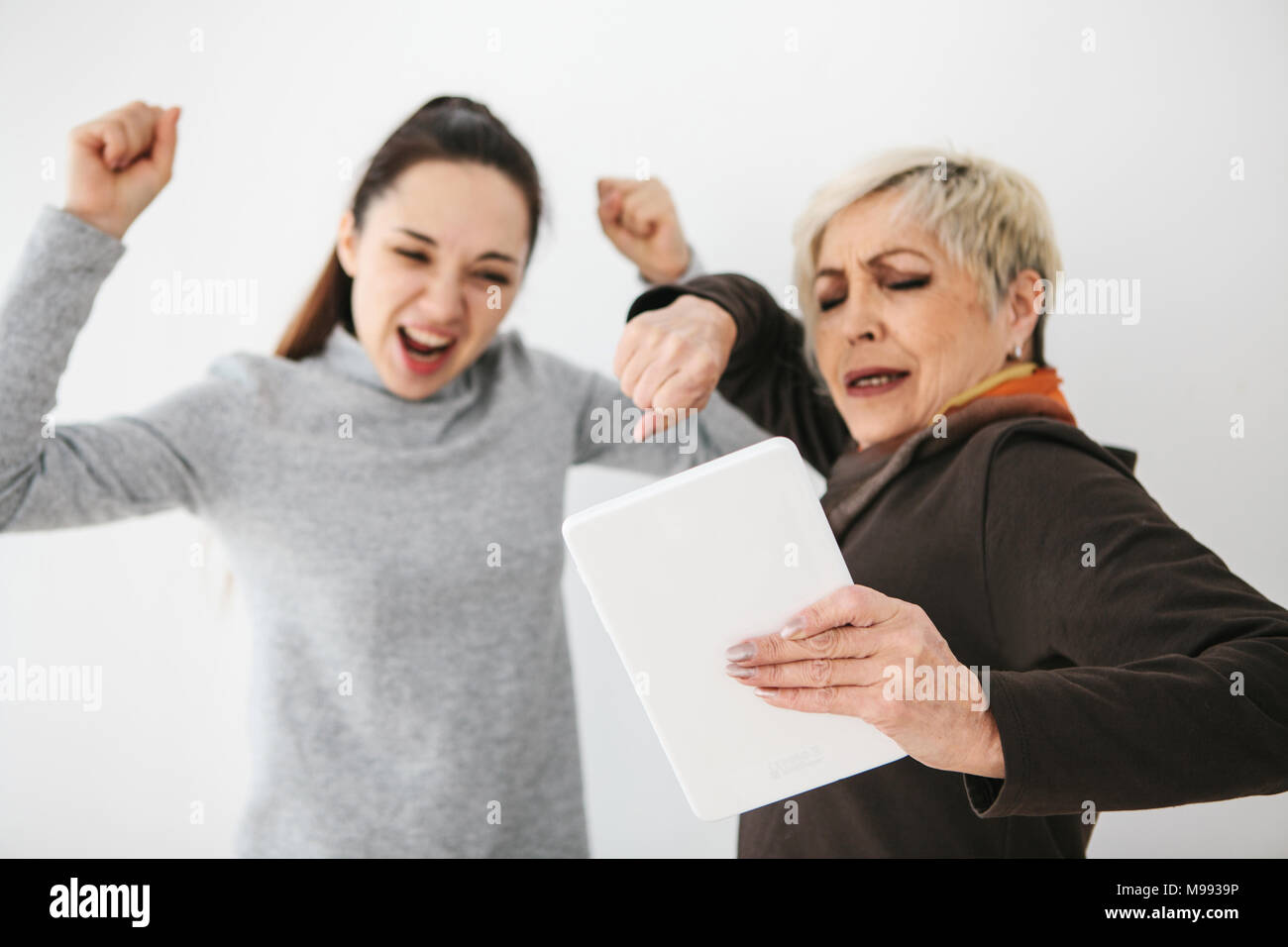 A young girl and an elderly woman look at something interesting on the tablet and show emotions. Communication, joint pastime of young and old people. - Stock Image