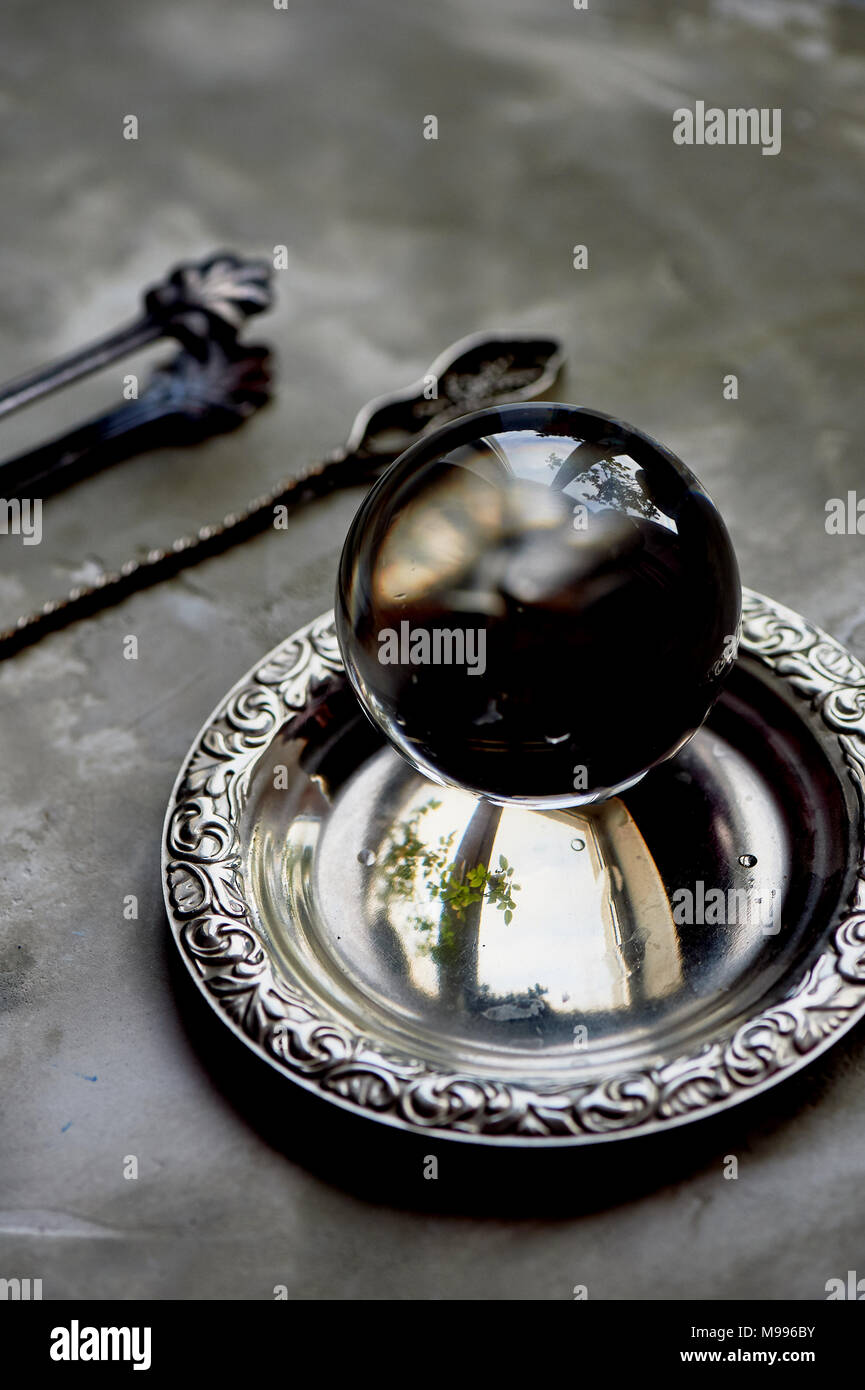 the glass ball lies on an old saucer.Old appliances. Grey concrete background - Stock Image