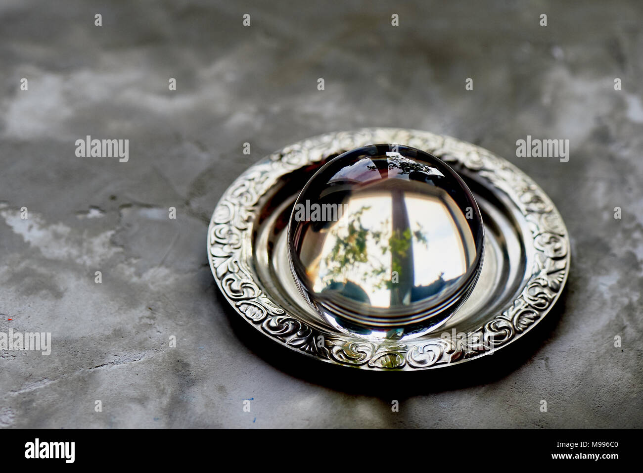 the glass ball lies on an old saucer. Grey concrete background - Stock Image