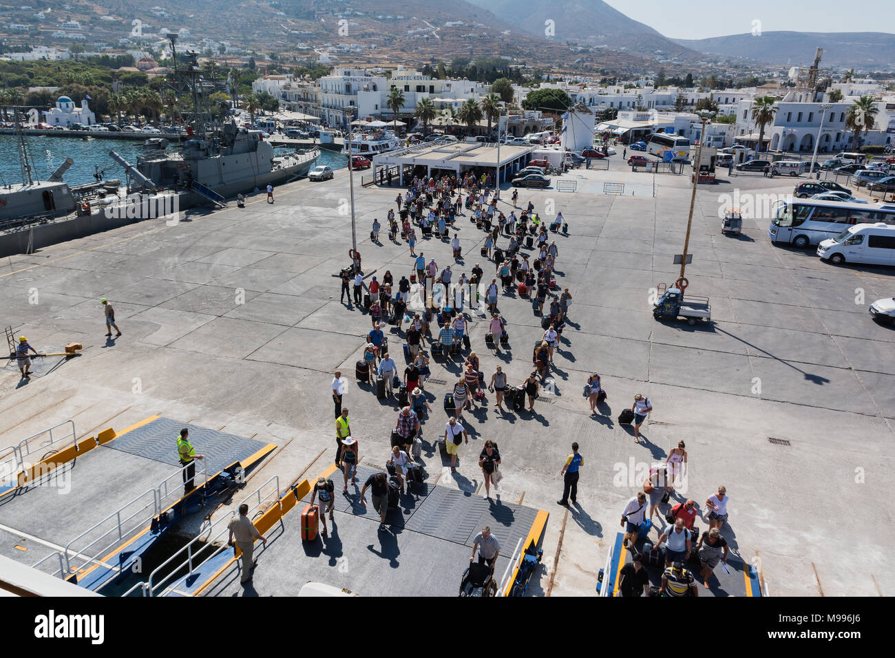 PAROS, GREECE - SEPTEMBER 17, 2016: Passengers and cars embark on a ship at the port of Paros in Greece. Paros is a beautiful Cycladic island visited  - Stock Image