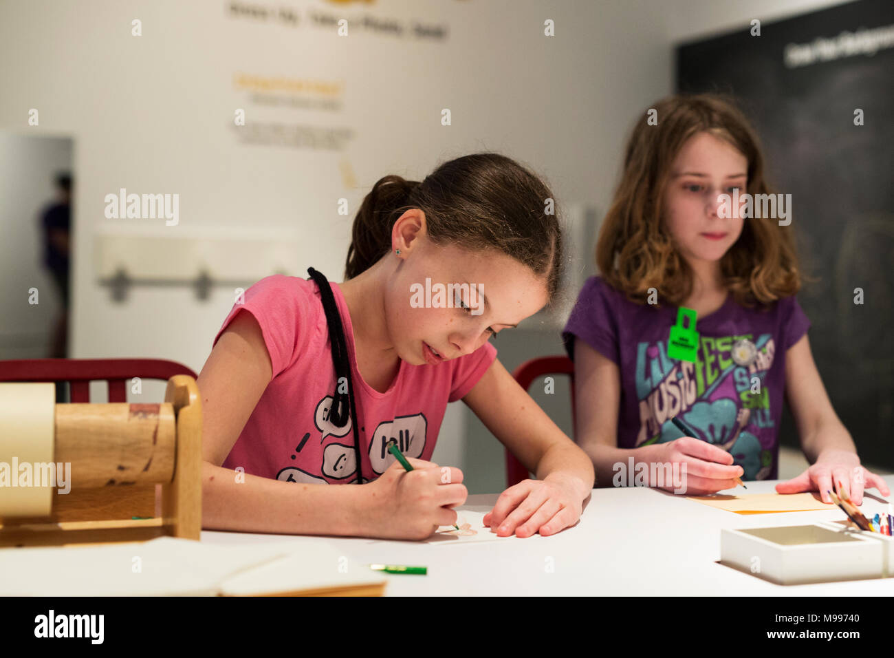 Two school age children (girls) drawing - Stock Image