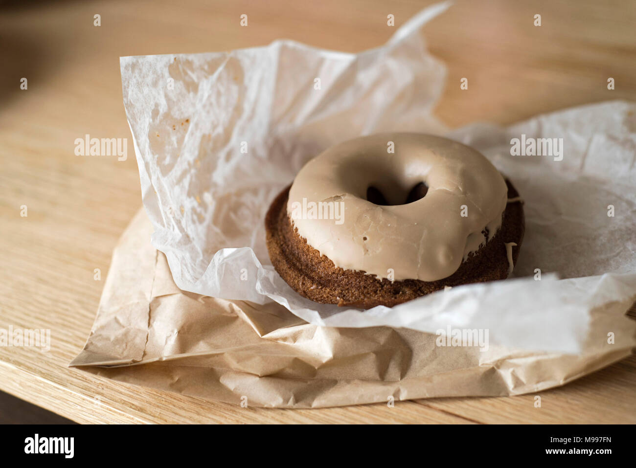 Ready to Eat Gluten-Free Donut on Parchment Paper and Brown Paper Bag - Stock Image