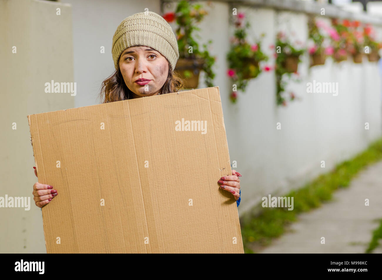 Outdoor view of homeless woman holding up blank cardboard sign - Stock Image