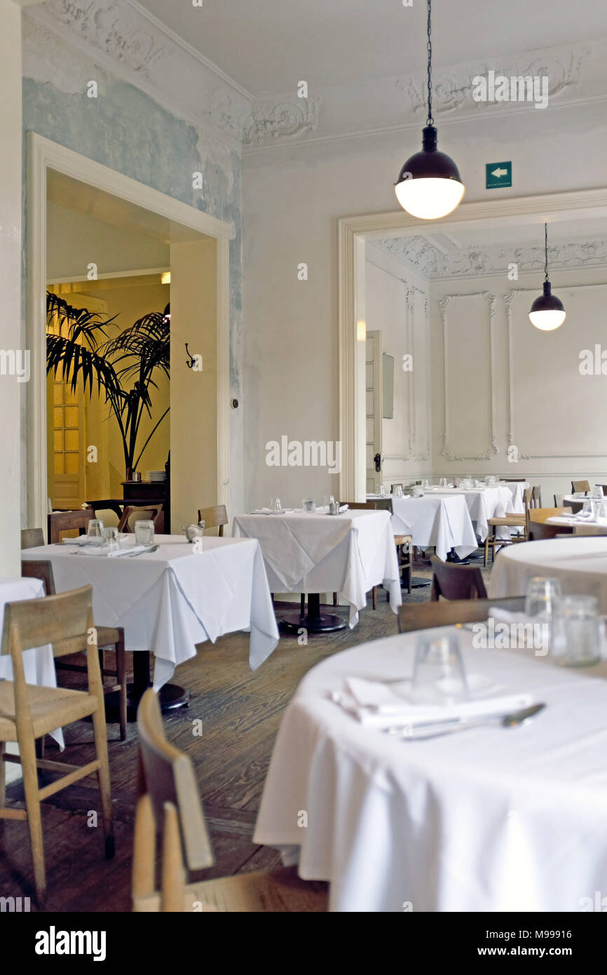 White-tablecloth fine dining establishment with empty tables. - Stock Image