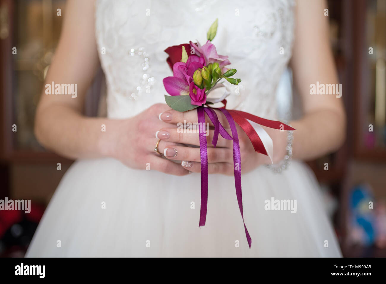 Bride holds flower bouquet for his beloved, close-up. Wedding day - Stock Image