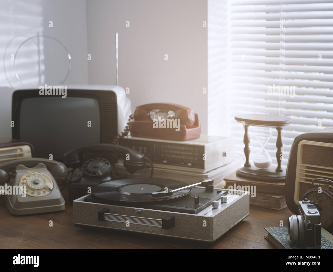 Vintage retro revival objects and second-hand appliances collection on a table: record player, television, radio and rotary dial telephones - Stock Image