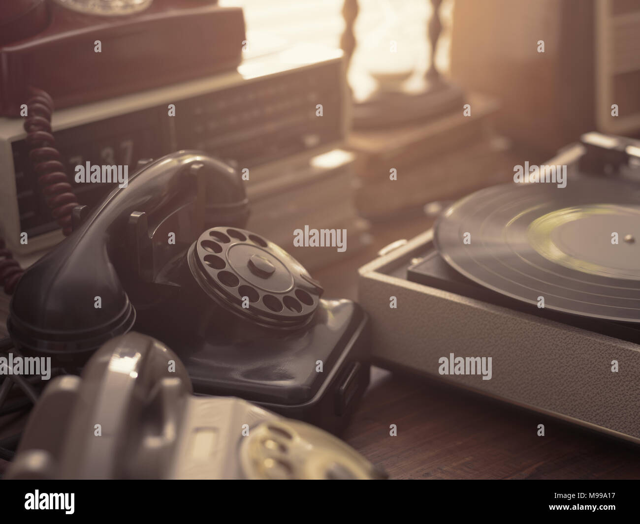 Vintage retro revival objects and appliances assortment on a table, rotary dial telephones and record player on the foreground - Stock Image