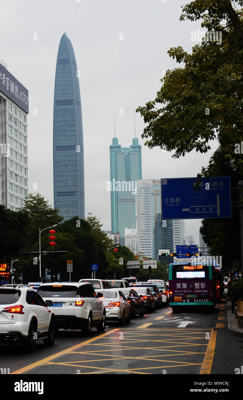 Traffic on Shennan Road with the KK100 skyscraper in the background. - Stock Image