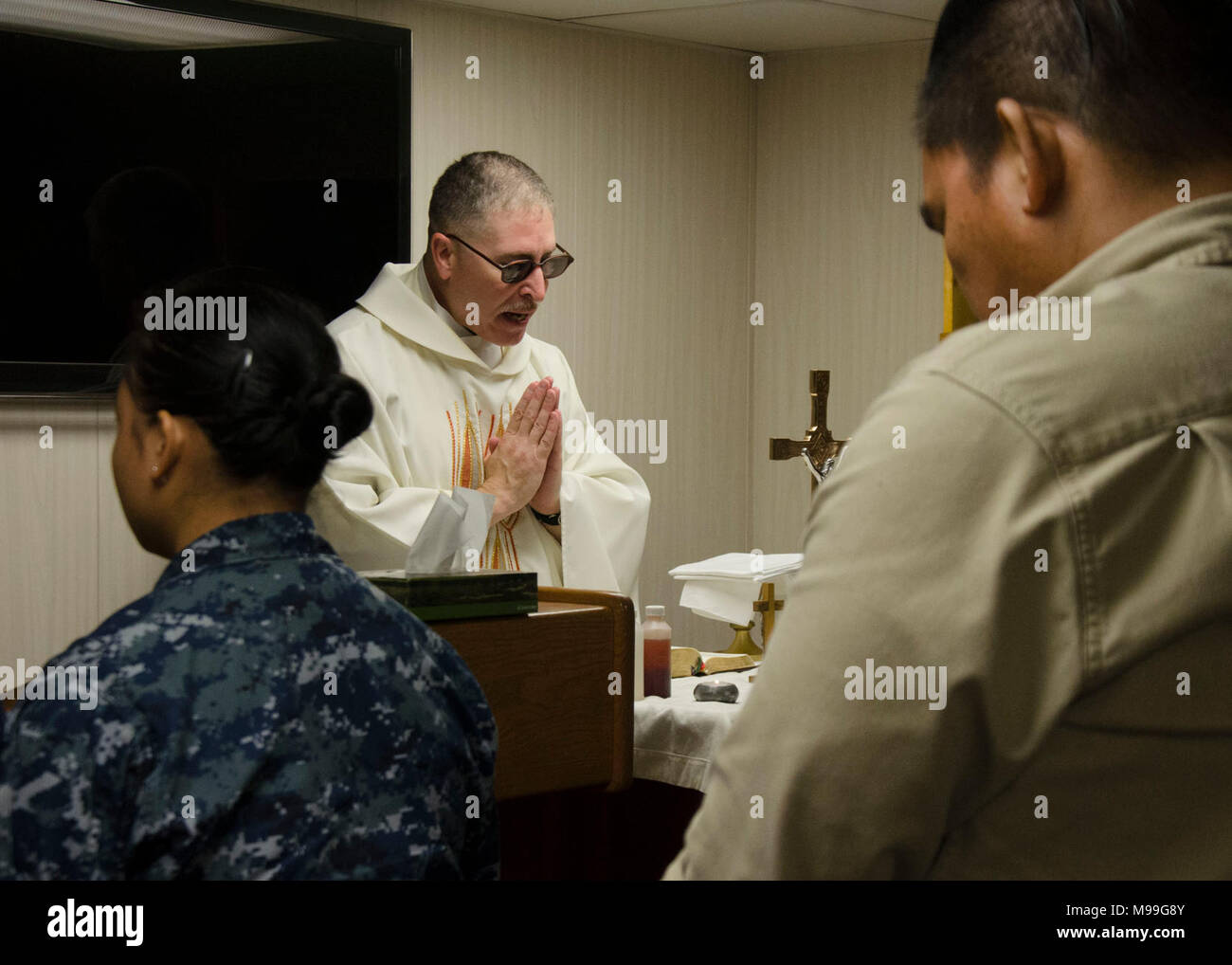 POLARIS POINT, Guam (Feb. 22, 2018) Lt. Cmdr. Andrew Colvin, a Naval Base Guam Command Chaplain, celebrates Roman Catholic Mass in the Conway Chapel aboard the submarine tender USS Frank Cable (AS 40), Feb. 22. Frank Cable, forward-deployed to Guam, repairs, rearms and reprovisions deployed U.S. Naval Forces in the Indo-Pacific region. (U.S. Navy - Stock Image
