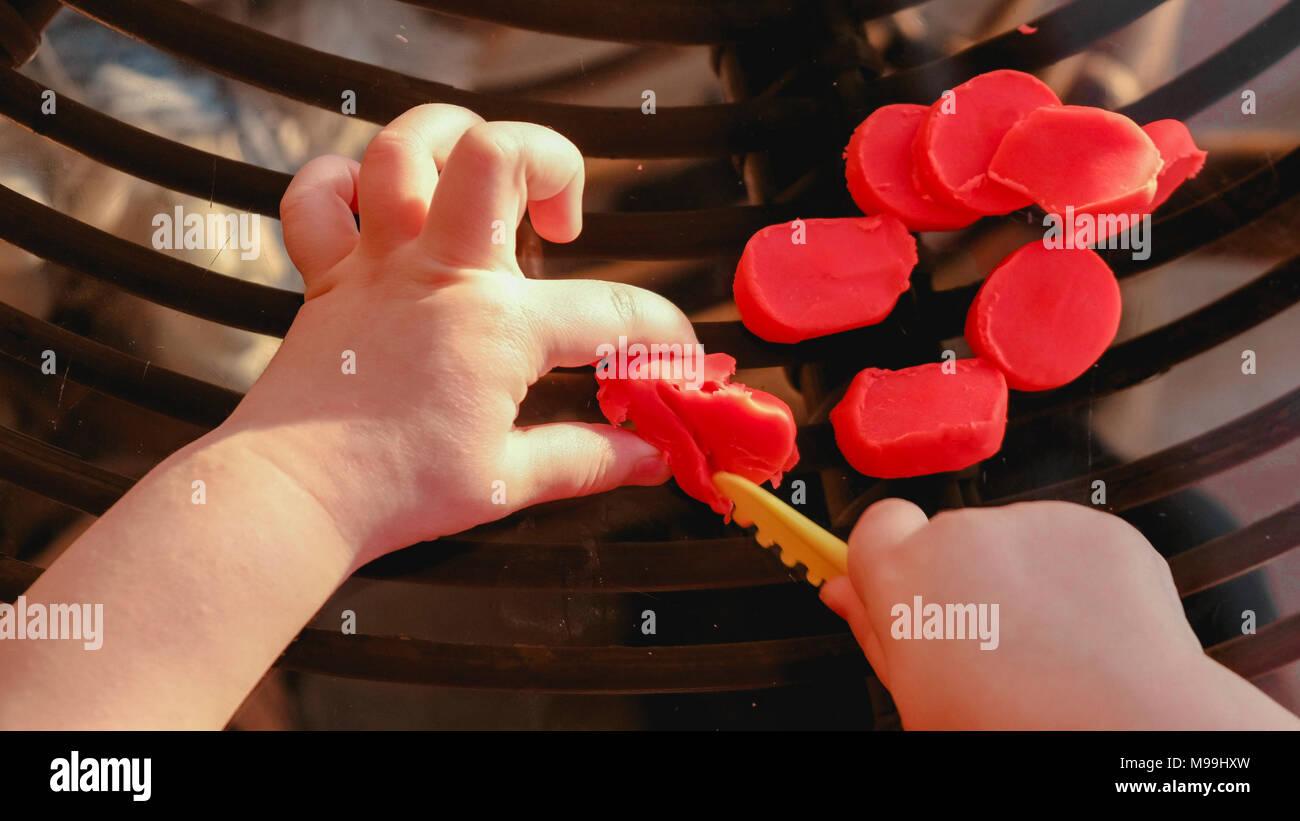 baby hands cutting plasticine - fine motor skill develop dexterity - pov above view - Stock Image
