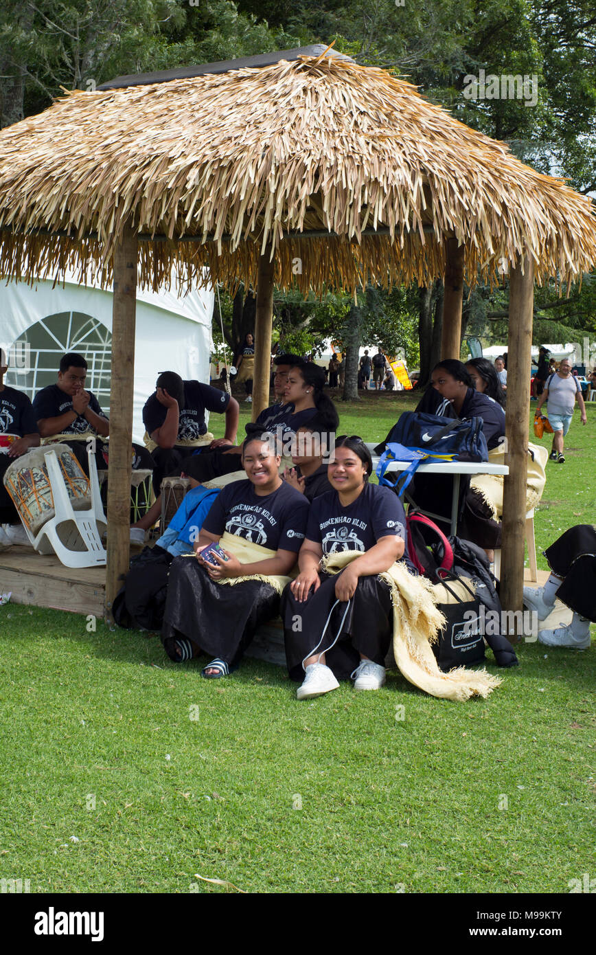 Spectators from Birkenhead College watch dance performances from the shade of a fale at the Pasifica festival , Auckland - Stock Image