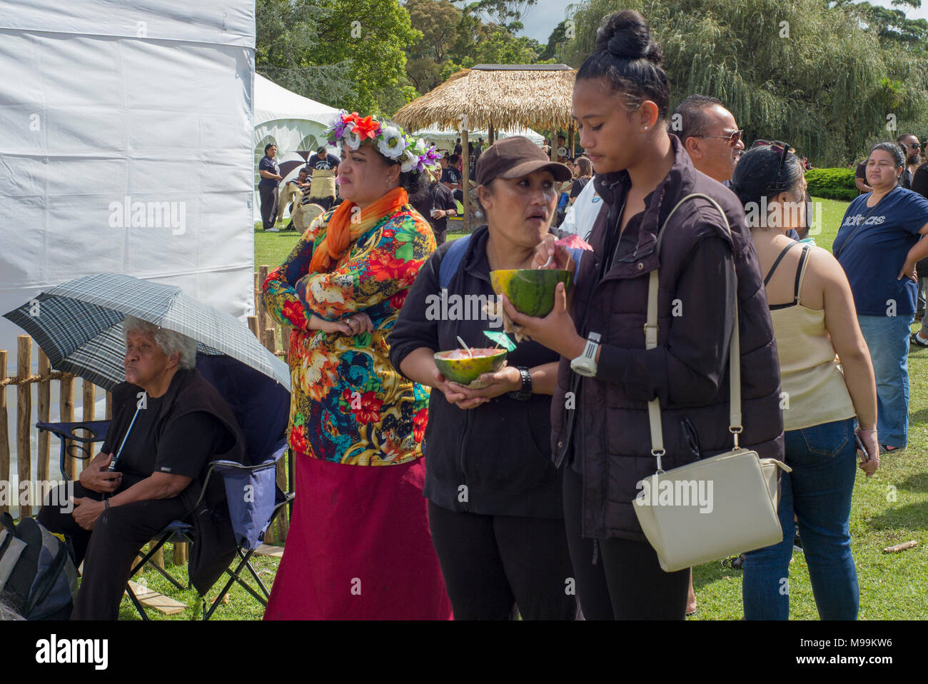 A group of people at Pasifica Festiva; Auckland. Some women are eating from half melons used as plates. - Stock Image