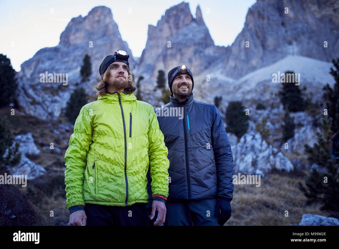Two confident men wearing headlamps in the mountains - Stock Image