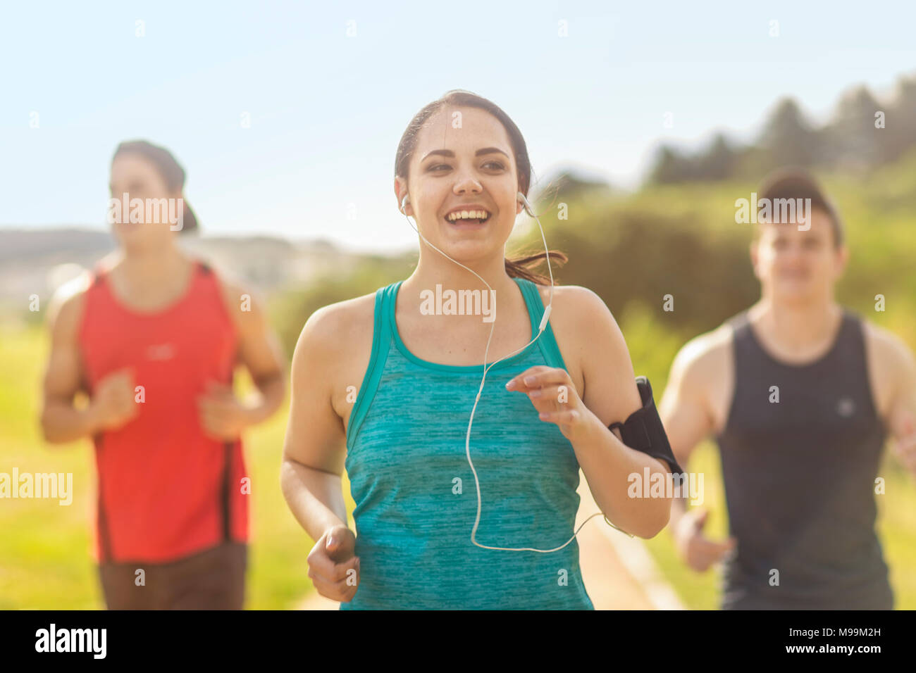 Group of friends running together - Stock Image