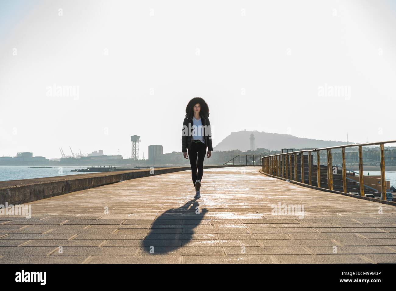 Spain, Barcelona, woman wearing hooded jacket walking on promenade - Stock Image