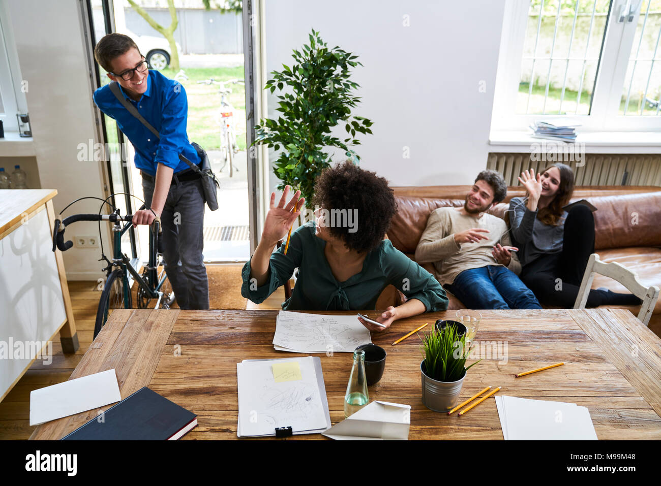 Coworkers waving at young man with bicycle arriving in modern office - Stock Image