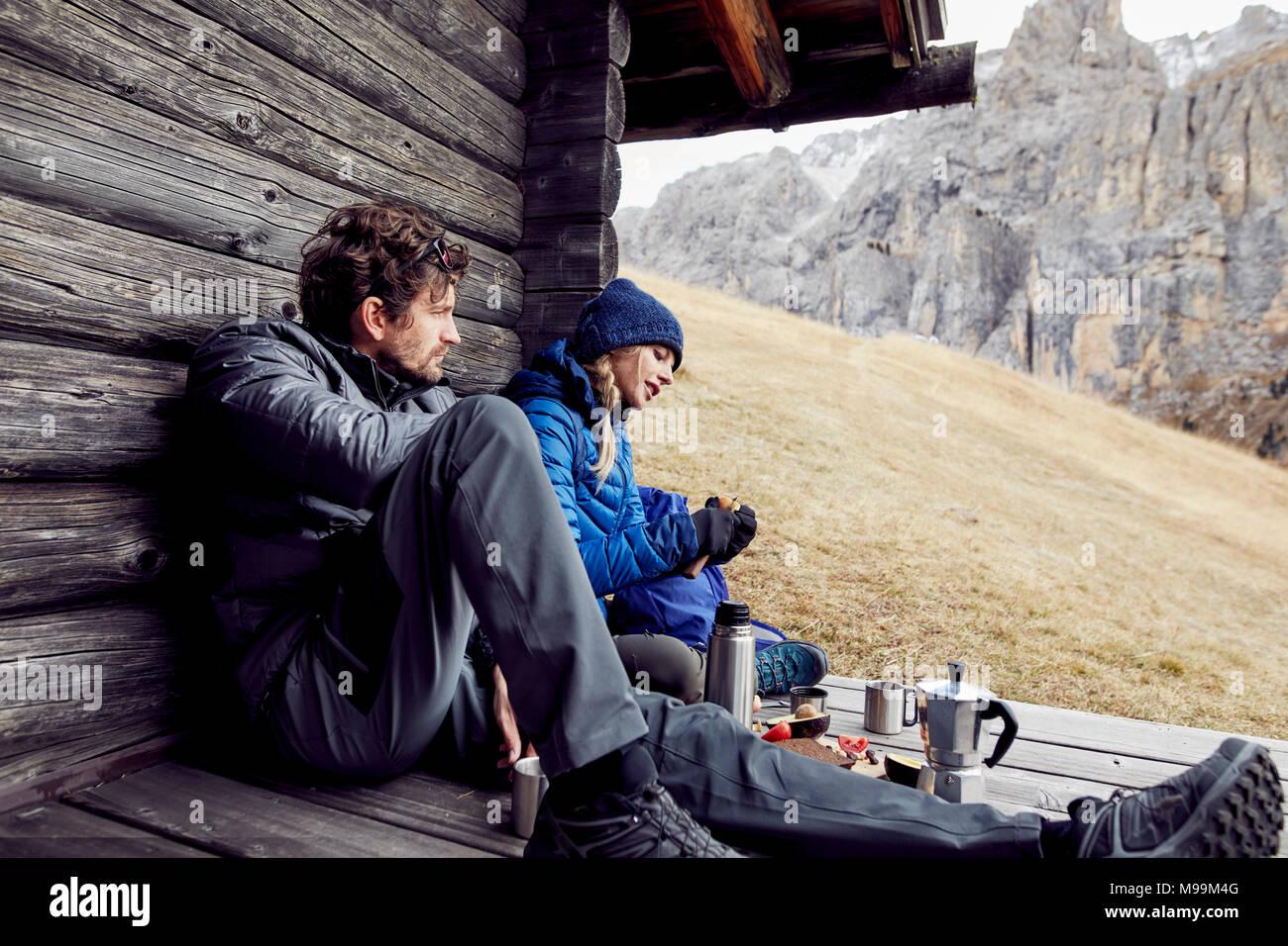 Couple having a break at mountain hut - Stock Image