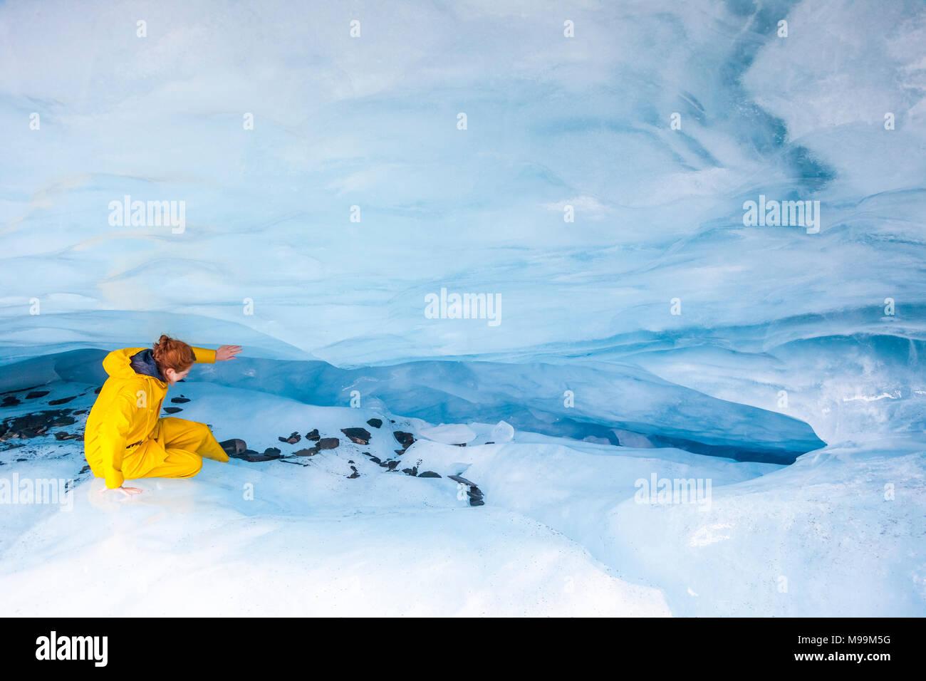 USA, Alaska, Valdez, Valdez Glacier young woman wearing oilskin, exploring ice cave - Stock Image