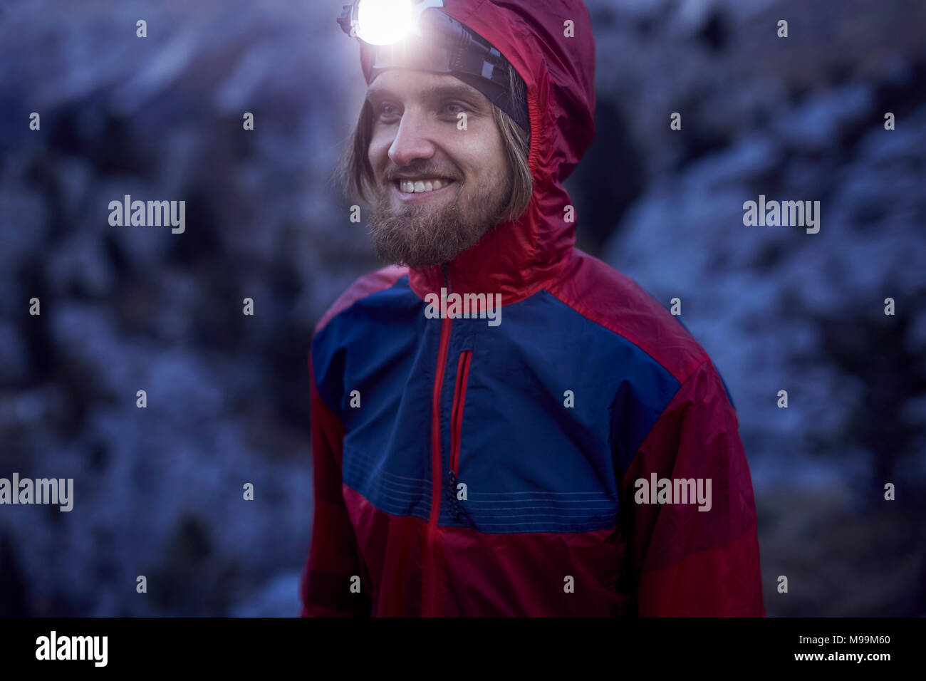 Portrait of smiling man wearing headlamp at dusk in the mountains - Stock Image
