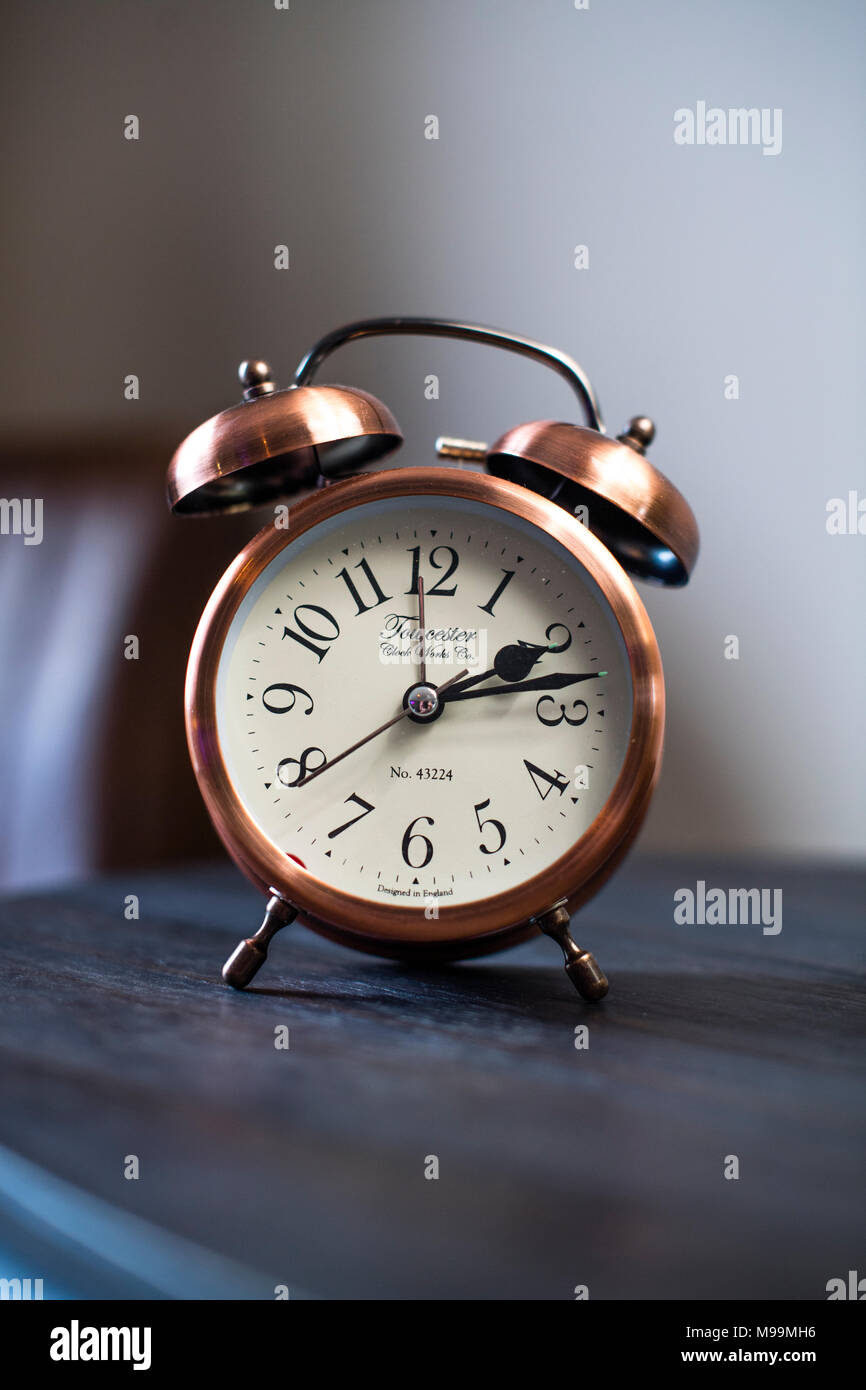 An old fashioned copper coloured bed side analogue pre digital alarm clock, made by the Towcester Clock Works, UK - Stock Image
